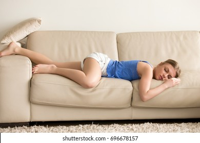 Tired funny young woman in summer everyday clothes stretches out and sleeps on sofa at home. Female student asleep in morning in living room after party, taking break for short sleep in middle of day