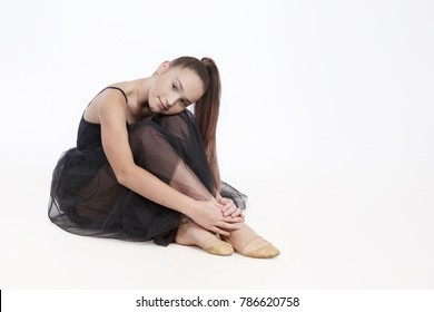 Tired girl gymnast wearing black transparent dress resting sitting on floor. Sportswoman isolated on white background looking at camera
