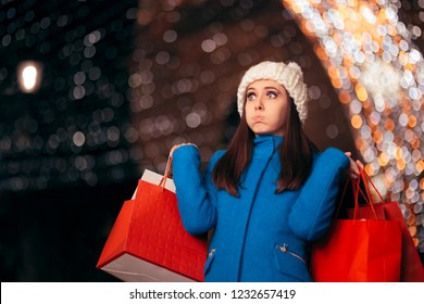 Tired Girl Holding Shopping Bags on Christmas Lights Decor. Exhausted stressed holidays buyer feeling fatigued