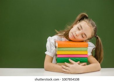 Tired girl sleeping on books in classroom. Space for text