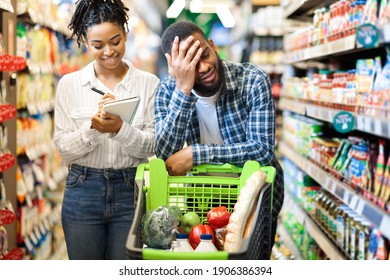 Tired Of Grocery Shopping. African Husband Waiting While Wife Buying Food Products Via Checklist Standing With Cart In Supermarket. Customers Purchasing Groceries. Consumerism And Stress Concept