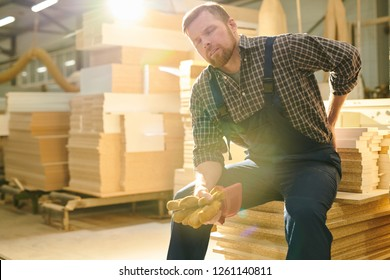 Tired handsome bearded manual worker with closed eyes sitting on stack of wooden plank and massaging lower back while feeling pain in back