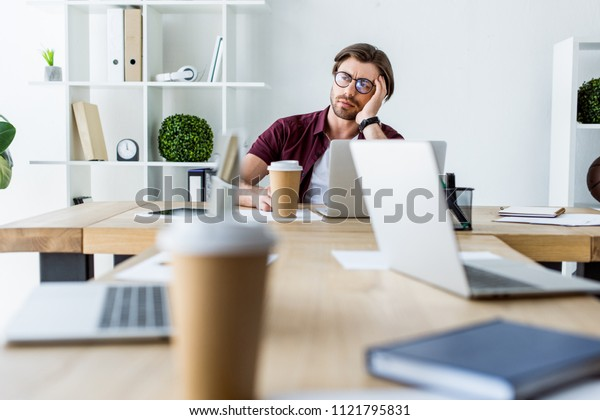tired handsome businessman working on startup project in office and looking away