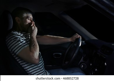 Tired handsome man falling asleep in car