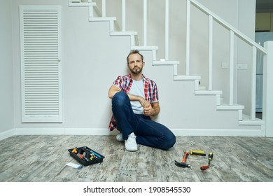 Tired handyman looking at camera, taking a break while sitting on the floor in apartment. Home repair hand tools on laminate flooring