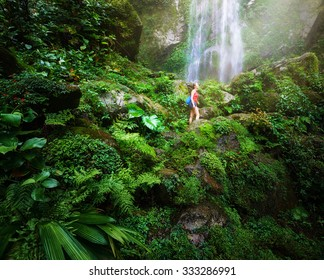 A tired but happy tourist woman looking at the waterfall in the Central America jungles Ecotourism concept image travel