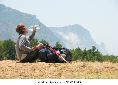 Tired hiker drinks water from a bottle