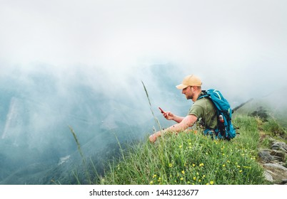 Tired hiker man with backpack browsing internet using smartphone enjoying cloudy valley bottom walking by the foggy cloudy weather mountain range . Active sports and navigation applications concept.