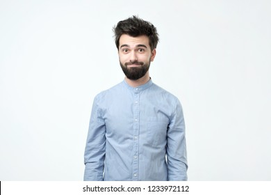 Tired hispanic man in blue shirt with beard looking confusedly at camera like he has no idea what is going on and try to smile