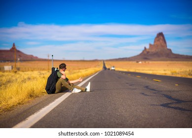 Tired hitch-hiker with suitcase sitting on a scenic road in Arizona, with his thumb up. Concept of travel, journey, holidays, vacation.