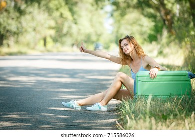 Tired Hitchhiking girl in a summer dress sitting on a road with a green plastic  case.  Road adventure concept