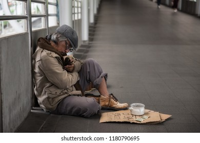 Tired Homeless old man or beggar hold bottle of beer and sleep at city sky walk. Poverty and social issue concept.