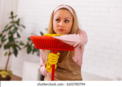 Tired housewife cleaning living room with a broom.