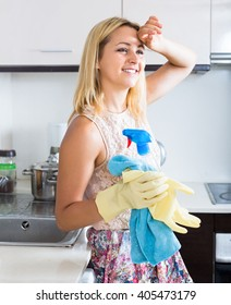 Tired housewife mops her brow after cleaning kitchen