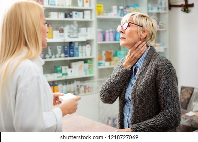 Tired, ill mature woman holding her throat and explaining problems to a beautiful young female pharmacist. Thyroid gland problems. Medicine, healthcare and pharmaceutics concept