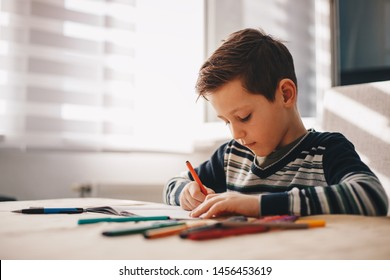 Tired kid boy at home making homework writing letters