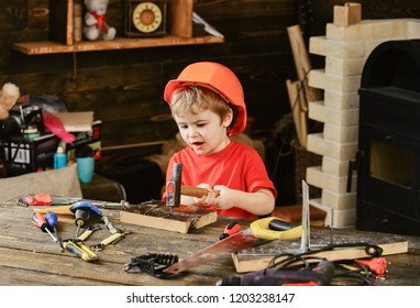 Tired kid playing in workshop. Small boy hammering nail. Little child in orange helmet sitiing at working desk.