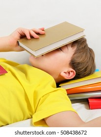 Tired Kid sleep with the Books on the Bed