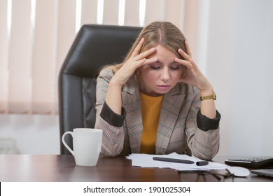 Tired lady boss sitting at table in office