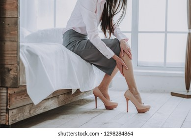 Tired lady touching her legs with arms while sitting in bedroom after returning home from job