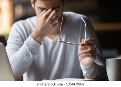 Tired of laptop businessman taking off glasses feel eyestrain close up focus on eyewear, man suffers from dry eyes tension massaging nose bridge relief discomfort, bad sight or vision problems concept