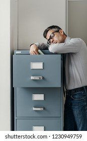 Tired lazy office worker leaning on a filing cabinet and sleeping, he is falling asleep standing up; stress, unproductivity and sleep disorders concept