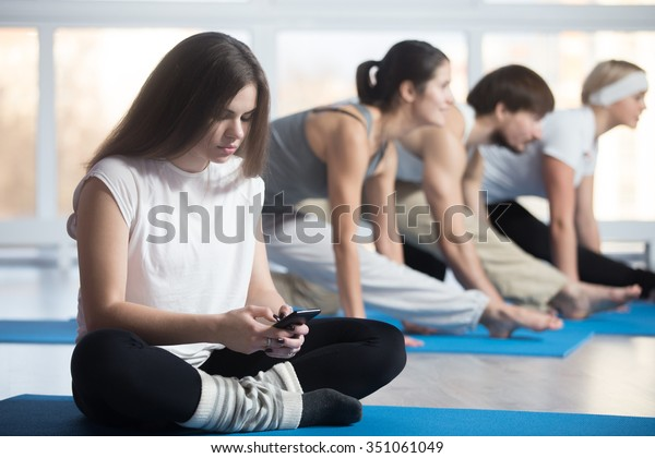 Tired or lazy woman sitting cross-legged, resting during practice in sports club, using phone, reading, sending or typing message, group of attractive fit young people working out on the background
