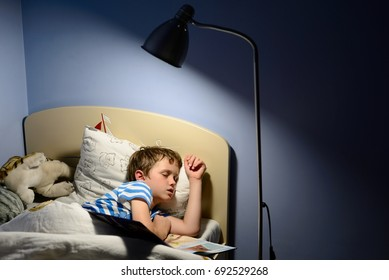 Tired little boy child fell asleep during reading a book in bed