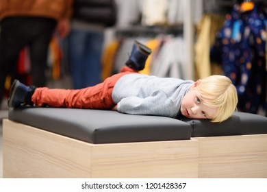 Tired little boy during shopping with parents. Fashion clothes for kids. Child in shopping center/mall or baby apparel store