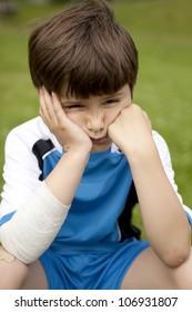 tired little boy sitting on soccer ball