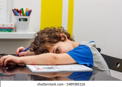 Tired little boy sitting at the table, with hishead on his arm, writing in her notebook while doing homework. Concept of a large number of assignments at school