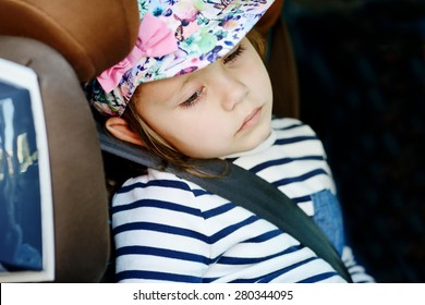 tired little girl in the car seat