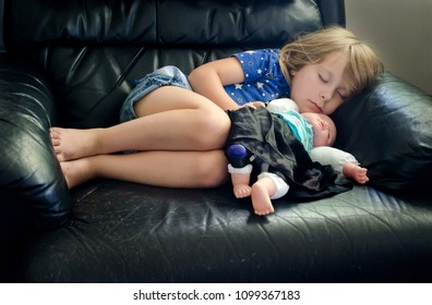 Tired little girl  with her favorite doll falls asleep in Grandpa's big leather chair