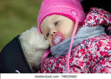 Tired little girl outdoors with a pacifier