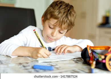 """Tired little kid boy at home making homework at the morning before the school starts. Little child doing excercise, indoors. Boy write """"This is a story"""" in German"""