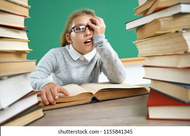Tired little schoolgirl around books. Photo of girl in classroom. Education concept