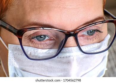 Müde Blick auf den Arzt im Moment einer Pause für die Pause. Eine medizinische Schutzmaske bedeckt das Gesicht.
