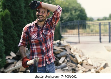 Tired lumberjack is finishing his work and smiling