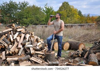 Tired lumberjack get rest and drink beer. Lumberjack drink cold beer to refresh after hard work