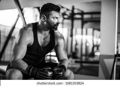 Tired male boxer sitting on stool in gym