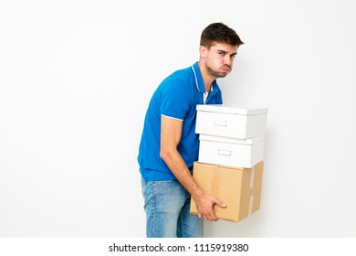 tired man in a blue T-shirt carrying very heavy cardboard boxes, on white background