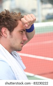 Tired man by tennis court