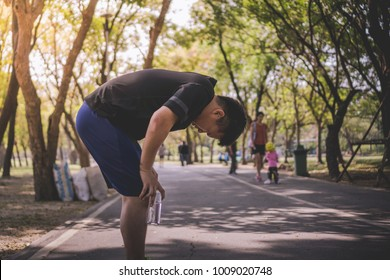 a tired man exhausted after an extreme exercise activity, running along the road path, holding a bottle of drinking water while resting at the peaceful park  with many tree for his health
