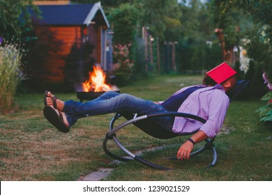 Tired man fell asleep while reading with a book on his face. Guy sleeping on a rocking chair (rocker) in his garden.