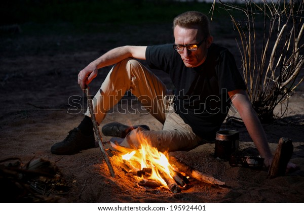 A tired man with glasses near campfire
