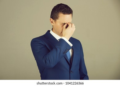 Tired man, handsome businessman or boss feeling headache with stylish hair, haircut in fashionable blue formal suit, white shirt and tie on grey background. Business. Stress and problems