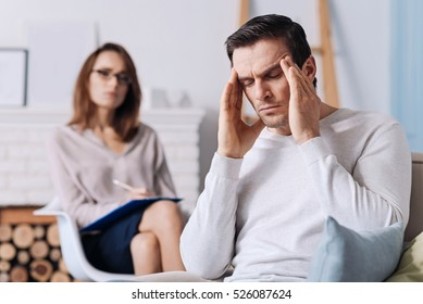 Tired man having consultation with psychologist