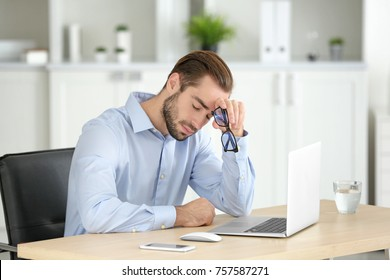 Tired man with laptop in office