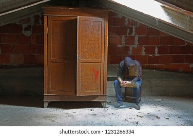 tired man like a soul sitting on a chair in the attic and a wooden wardrobe