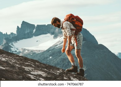 Tired Man in mountains with backpack Norway Travel lifestyle hiking hard trek concept adventure summer vacations